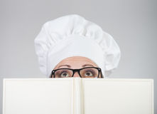 Woman in chef's hat looking over the cookbook Royalty Free Stock Photo