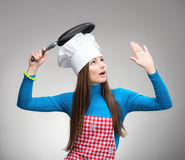 Woman in chef's hat with the pan under her head looking up Stock Image