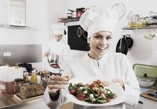 Woman chef serving fresh salad Stock Image