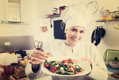 Woman chef serving fresh salad. Portrait of smiling women chef serving fresh salad at restaurant's kitchen Royalty Free Stock Images