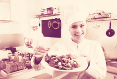 Woman chef serving fresh salad. Smiling women chef serving fresh salad at restaurant`s kitchen Royalty Free Stock Photography