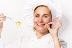 Woman chef showing a sign perfect, with pasta noodle on fork, ov Stock Photos