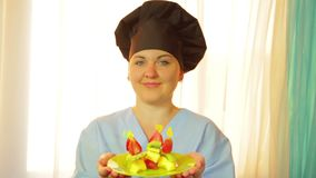 The woman - the chef smiles and holds a plate with a fruit dessert in her hands. Control sunlight from the window. The middle plan stock video footage