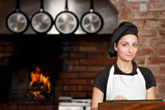 Woman Chef standing in the kitchen with wood oven. Woman Chef is standing at the kitchen entrance with the wood oven in the background in a pizza restaurant stock photos