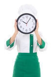 Woman chef in uniform holding office clock behind her face isola Stock Photos