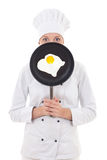 Woman in chef uniform holding skillet with frying egg behind her Royalty Free Stock Images