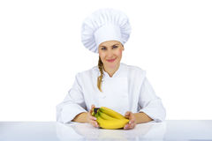 Woman chef in uniform. Isolated on white background with bananas Stock Images
