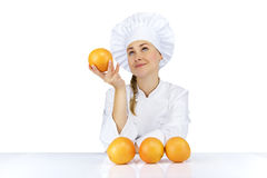 Woman chef in uniform. Isolated on white background with oranges Royalty Free Stock Photos