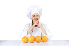 Woman chef in uniform. Isolated on white background with oranges Stock Images