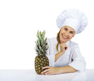 Woman chef in uniform. Isolated on white background with pineapp Stock Photo