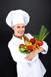 Woman chef with vegetables on her hands over dark background Stock Photography