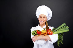 Woman chef with vegetables on her hands over dark background. Smilingwoman chef with vegetables on her hands over dark background Royalty Free Stock Images