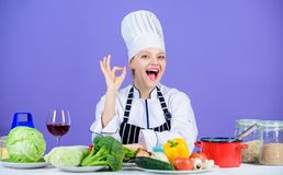 Woman chef wear hat apron near table ingredients. Girl adorable chef teach culinary. Best culinary recipes to try at stock image