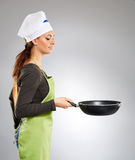 Woman chef with a wok Stock Images