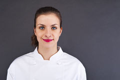 Woman cheff over dark backgrund. In uniform royalty free stock photography