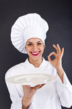 Woman cheff over dark backgrund. In uniform with plate stock photography