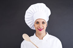 Woman cheff over dark backgrund. In uniform with spoon royalty free stock photos