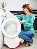 Woman cheking  clothes near washing machine Royalty Free Stock Photos