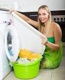 Woman cheking white clothes near washing machine Stock Photos