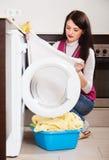 Woman cheking white clothes near washing machine Royalty Free Stock Photos