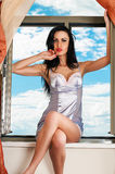 Woman in a chemise sitting on the windowsill Royalty Free Stock Photo
