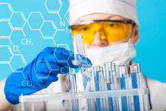 Woman chemist examines test tube Stock Photo