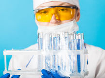 Woman chemist examines test tube Royalty Free Stock Photos