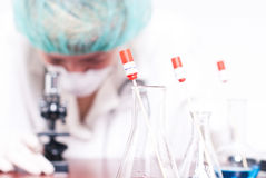 Woman in chemistry lab. Woman testing and analyzing data on microscope Stock Photo