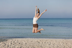 Woman cherfull jumping on beach landscape. Girl young cheerful woman jumping in the air on the beach in the sand in the morning on the sea in summer vacation Stock Images