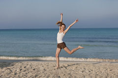 Woman cherfull jumping on beach landscape. Girl young cheerful woman jumping in the air on the beach in the sand in the morning on the sea in summer vacation Stock Photography