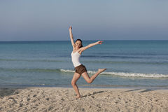 Woman cherfull jumping on beach landscape. Girl young cheerful woman jumping in the air on the beach in the sand in the morning on the sea in summer vacation Stock Photos