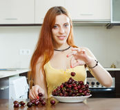 Woman with cherry in domestic kitchen Royalty Free Stock Image