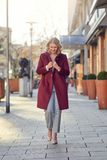 Woman in cherry red coat walking alone towards camera Royalty Free Stock Image