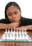 Woman with chess board. Black woman with puzzled expression studying chess board Royalty Free Stock Photo