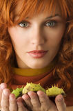 Woman with chestnut. Close up of young red haired woman with some wild chestnut in hands Royalty Free Stock Photography