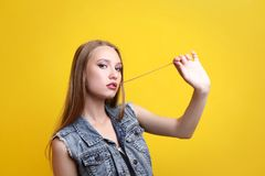 Woman chewing gum. Young woman chewing gum on yellow background stock photo
