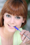 Woman chewing on a pen Stock Photo