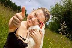 Woman with chicken lifts thumb up Royalty Free Stock Photo