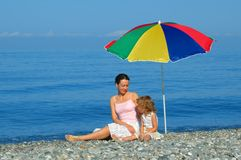The woman and child on the beach. The woman and child sitting under an umbrella on the beach Stock Image