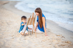 Woman and child on the beach. Woman and child in blue and white dress sit on the beach and draw on the easel stock photo