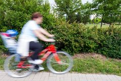 Woman with child on bicycle Stock Images
