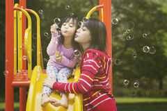 Woman and child blow soap bubbles Stock Images