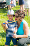 Woman and child blowing soap bubbles. Smiling woman and toddler boy with Mickey Mouse hat blowing soap bubbles on the Festiwal Baniek Mydlanych at a park on Royalty Free Stock Photos