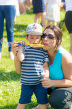 Woman and child blowing soap bubbles. Woman and toddler boy with Mickey Mouse hat blowing soap bubbles on the Festiwal Baniek Mydlanych at a park on August 2017 Royalty Free Stock Photography