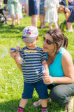 Woman and child blowing soap bubbles. Woman and toddler boy with Mickey Mouse hat blowing soap bubbles on the Festiwal Baniek Mydlanych at a park on August 2017 Royalty Free Stock Image