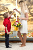 Woman and child with bouquet of flowers. Spring family holiday concept. Women`s day. Young son gives mom flowers.women`s day royalty free stock photography