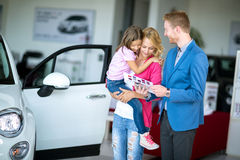 Woman with child in  car dealership looking at brochure with sal Royalty Free Stock Photos