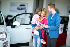 Woman with child in  car dealership looking at brochure with sal Stock Images