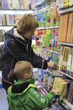 A woman with a child choose a book in a bookstore stock photos