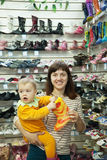 Woman with child chooses baby boots Stock Photo